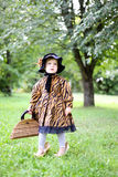 Little cute girl in hat and cloak  with handbag in autmn pa Stock Photo