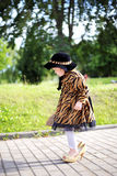 Little cute girl in hat and cloak  with handbag in autmn pa Stock Image