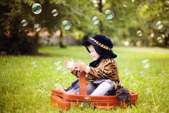 Little cute girl in hat and cloak  sitting on suitcase in a Stock Image