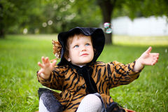 Little cute girl in hat and cloak  sitting on suitcase in a Royalty Free Stock Images