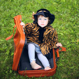 Little cute girl in hat and cloak  sitting on suitcase in a Stock Photos