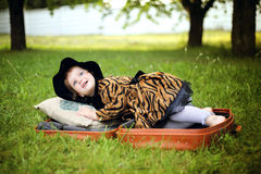 Little cute girl in hat and cloak  sitting on suitcase in a Royalty Free Stock Photography