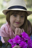 Little cute girl in a hat holding a bouquet of flowers Stock Photography