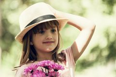 Little cute girl in a hat holding a bouquet of flowers Stock Photo