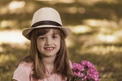 Little cute girl in a hat holding a bouquet of flowers. Portrait of a cute little girl smiling while holding a bouquet of flowers. Copy space Royalty Free Stock Photography