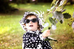 Little cute girl in hat and sunglasses in autmn park Stock Image