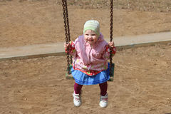 Little cute girl in hat swings stock image