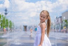 Little cute girl have fun in open street fountain Royalty Free Stock Photos