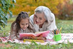 Girl with her grandmother reading Stock Image