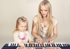 little cute girl with her mom playing on synthesizer Stock Photo