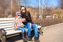 Little cute girl with her mother walking on a sunny day outdoors Stock Photo