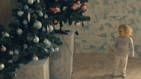 Little cute girl hides behind Christmas tree and then run away. Little blonde baby girl hides behind decorated Christmas tree and then comes out and smiling stock video footage