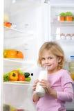 Little cute girl holding bottle of milk near open Stock Photos