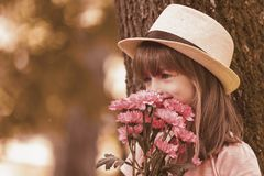 Little cute girl  holding a bouquet of flowers. Little cute girl with a hat holding a bouquet of flowers and enjoy nature, outdoors Stock Images