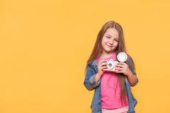 Little cute girl holding a lomo photo camera. A little cute girl holding a lomo photo camera  over yellow background. Trendy preschooler kid photographer with Royalty Free Stock Image
