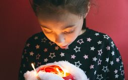 Little cute girl holding Santa`s hat with glowing garland inside on red background stock image