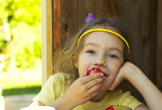 Little cute girl holding a strawberry in summer day Stock Photography