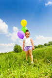 Little cute girl holding three flying balloons Stock Photography