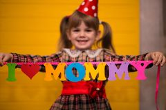 Little cute girl holds a garland with text `I love mommy` of colorful paper alphabet. Focus on text Royalty Free Stock Images