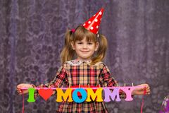 Little cute girl holds a garland with text `I love mommy` of colorful paper alphabet. Focus on girl Royalty Free Stock Photography