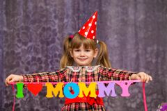 Little cute girl holds a garland with text `I love mommy` of colorful paper alphabet. Focus on girl Stock Image