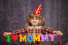 Little cute girl holds a garland with text `I love mommy` of colorful paper alphabet. Focus on text Stock Image