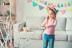 Little cute girl at home easter celebration concept in bunny ears decorating tree with eggs stock image