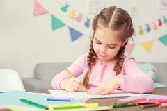 Little cute girl at home education concept sitting drawing greeting card for mom`s birthday royalty free stock images