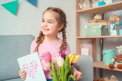 Little cute girl at home mother`s day celebration concept with tulips and greeting card royalty free stock photo