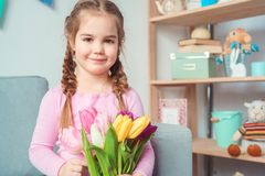Little cute girl at home mother`s day celebration concept holding flowers bouquet royalty free stock image