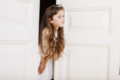 Little cute girl at home, opening door well-dressed in white dress, adorable milk fairy teeth Stock Photography