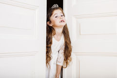 Little cute girl at home, opening door well-dressed in white dress, adorable milk fairy teeth Royalty Free Stock Photo