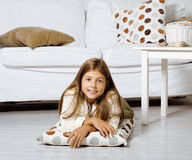 Little cute girl at home smiling. Laying on the floor stock photos