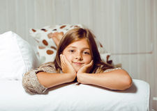 Little cute girl at home smiling. Sitting on sofa royalty free stock images