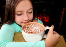 Little cute girl with hot chocolate by the fireplace. Royalty Free Stock Photos