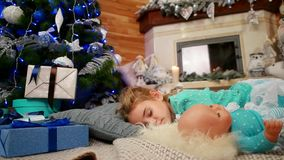Little cute girl hugging a doll during sleep, The child sleeps near a Christmas tree, sweet sleep in the living room stock video footage