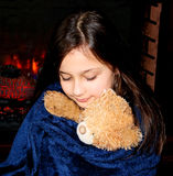 Little cute girl hugging teddy bear by the fireplace. Royalty Free Stock Images