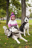 Little cute girl with husky dog outside Stock Photos