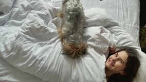 Little cute girl indoors and dog sleeping in bed. little girl teen brunette asleep on the bed lifestyle funny. Little cute girl indoors and dog sleeping in bed stock footage
