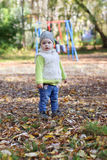 Little cute girl in jeans stands on playground Royalty Free Stock Image