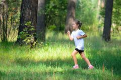 Little cute girl jogging in forest Royalty Free Stock Photography