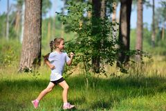 Little cute girl jogging in forest Stock Images