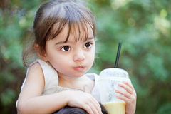 Little cute girl with juice. Cute little girl riding her mother's sholders with a glass of juice in hand Stock Photos