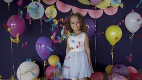 Little cute girl jumping under bright confetti celebrating her birthday party. Little cute girl jumping under bright confetti and celebrating her birthday party stock video