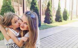 Little cute girl kissing her beautiful mum outdoor in the park Stock Photo
