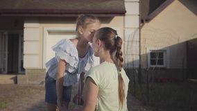 Portrait little cute girl kissing her mother standing in the backyard outdoors. Relationship mom and daughter. Real. The little cute girl kissing her mother stock video