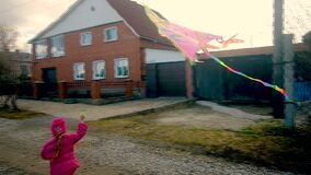 Little cute girl with a kite at the cottage. Running along the road