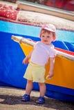 Little cute girl leaning on a boat. Little cute girl leaning on a colourful wooden boat in harbour in La Gomera island, Canary Islands, Spain royalty free stock photos