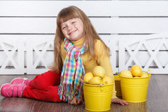 Little cute girl with lemons in two yellow buckets Royalty Free Stock Photo