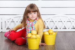 Little cute girl with lemons in two yellow buckets Royalty Free Stock Image